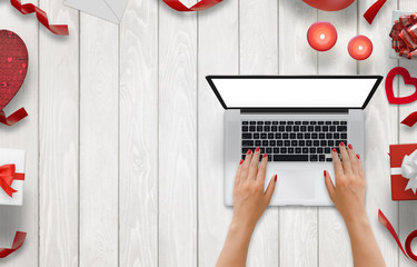 Girl work on laptop with isolated screen on a wooden background. Free space for text. Love decorations beside, gifts, candles, hearts