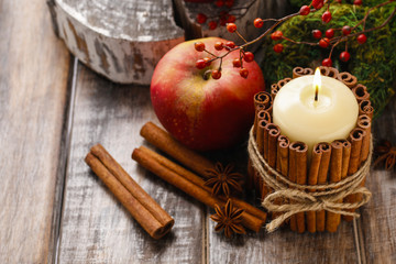 Candle decorated with cinnamon sticks and red apples