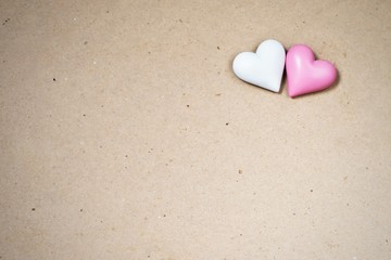 Two small wooden heart (white,pink) on paper background