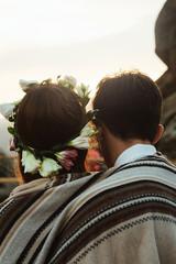 happy luxury couple newlyweds looking at sunset hugging under ru