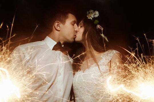 happy beautiful bride and elegant stylish groom holding firework