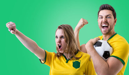 Brazilian couple fan celebrating on green background