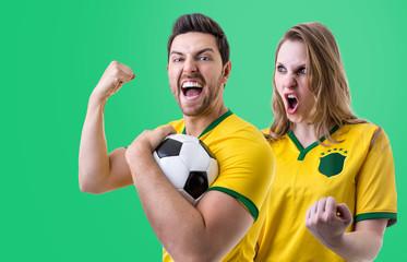 Brazilian couple fan celebrating on green background