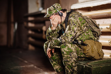Sad solider sitting with a black rifle