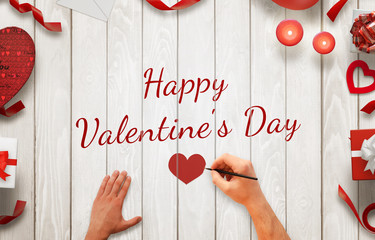 Man hand painting  Happy Valentines day message on a wooden background. Love decorations beside, gifts, candles, hearts