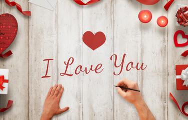 Man hand painting I love you message on a wooden background. Love decorations beside, gifts, candles, hearts