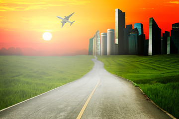 Asphalt road with green field along to buildings with airplane