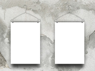 Close-up of two hanged paper sheets with clothes hangers on damaged concrete wall background