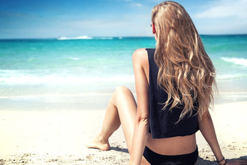 Blonde girl on the beach, relaxing.