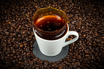 coffee cup with splash on coffee beans background