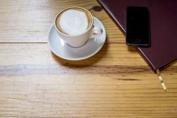 notebook with cup of coffee on wooden desk