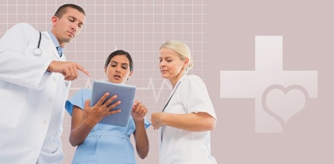 Composite image of doctors looking together at tablet