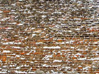 Wide red brick wall covered with snowflakes