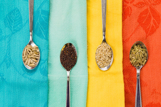 Spoon of sunflower sesame fennel mustard seeds for macrobiotic food on colorful background