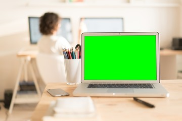 Green screen laptop computer and a glass with color pencils on wooden table, creative office on the background