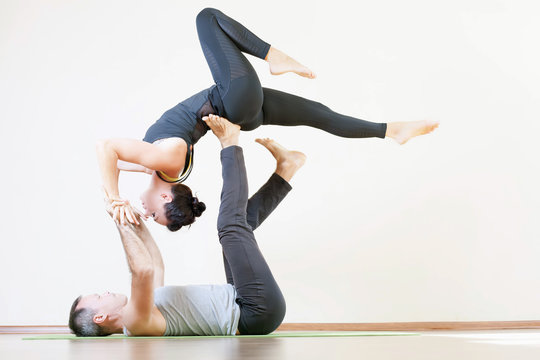 Man and woman doing acro yoga or pair yoga indoor
