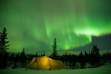 beleuchtetes Zelt mit Nordlichtern im Hintergrund