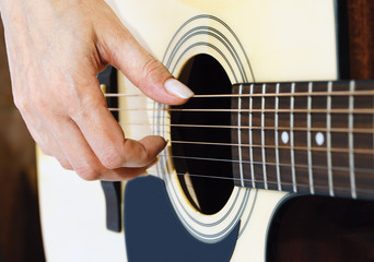 hand on an acoustic guitar