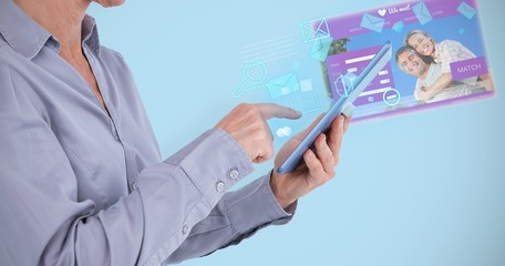 Composite image of businesswoman using her tablet