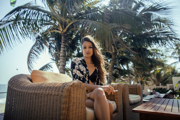 young pretty woman at swimming pool relaxing in chair, fashion look lingerie at hotel close up smiling cool vacations