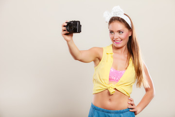 Pin up girl woman taking photo with camera.