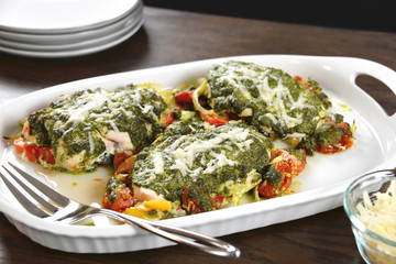 Tasty baked chicken breasts are covered with basil pesto sauce, fresh cherry tomatoes, yellow bell peppers and topped with melted parmesan cheese.