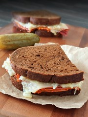 Reuben sandwiches with corned beef and melted Swiss cheese on wood