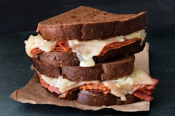 Stacked Reuben Sandwiches with corned beef and melted Swiss cheese against a dark slate background