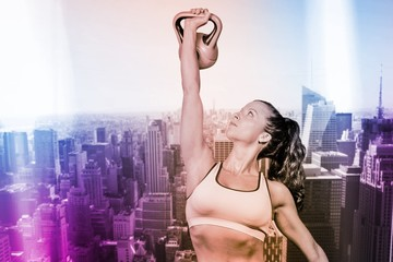 Composite image of woman lifting kettlebell
