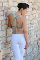 Back of an attractive young woman in exercise clothes and natural stone work wall