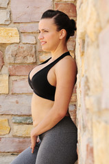 Fitness model against a stone wall sideways with a black top and yoga pants