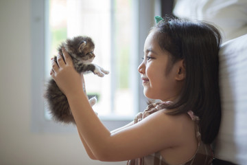 Adorable little asian girl kissing her kitten