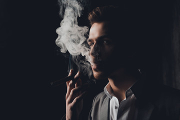 Handome man in suit on the black background smoking a cigar