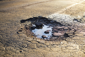 Obraz A road damaged by rain and snow, that is in need of maintenance. Broken asphalt pavement resulting in a pothole, dangerous to vehicles.  - fototapety do salonu