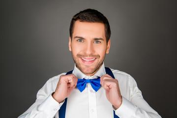 Smiling man binding a bow