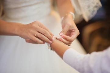 bride getting bracelet dressed