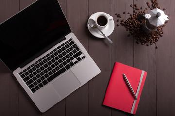 tazza di caffè con grani e mocca su sfondo di legno vicino ad un quaderno rosso e un computer