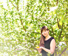 Portrait of beautiful girl with bouquet of yellow dandelions outdoor in spring, focus on eyes, apple blossom background
