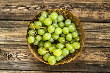 Bunch of green grapes in the basket on wooden planks