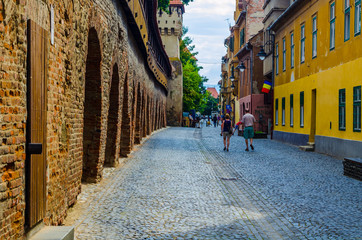 Unidentified people wander along the medieval defense wall and The Carpenters' Tower in Sibiu city where a lot of small streets remind medieval character of this city part