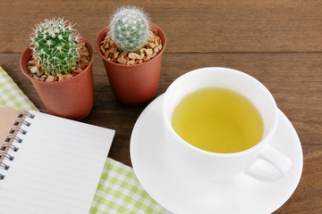 The cup of Japanese green tea and little cactus in plant pot and small note book with green cotton fabric on wooden planks.