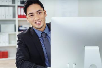 zufriedener junger mann im büro arbeitet am pc