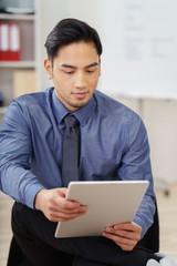 mann im büro liest die nachrichten auf seinem tablet