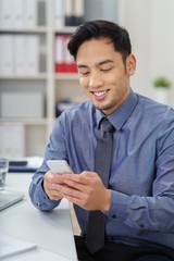 mann im büro schaut lächelnd auf sein handy