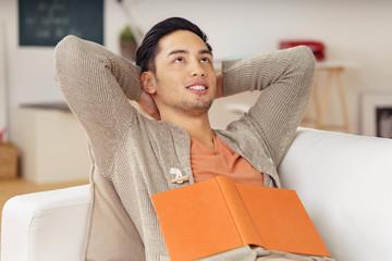 entspannter mann mit einem buch auf dem sofa