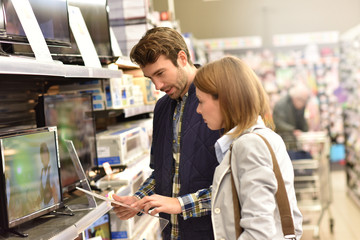 Couple in department store choosing television set