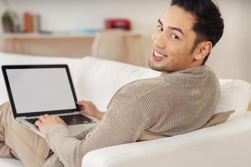 junger mann sitzt mit laptop zuhause auf dem sofa
