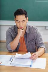 student liest konzentriert in unterlagen