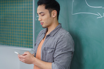 student im kursraum schaut auf sein handy