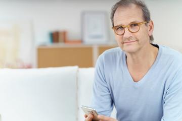 mann sitzt auf dem sofa und hält sein smartphone in der hand